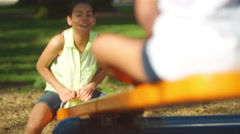 Young girl on a see-saw in a park - stock footage