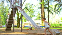 Young girls going down a slide at a park Stock Footage