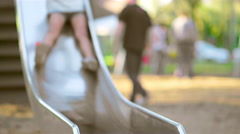 Young girl comes down a slide and smiles Stock Footage