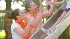 Mother and father watching thier children come down a slide Stock Footage