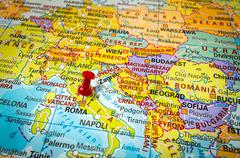 Red thumbtack in a map, pushpin pointing at Rome city - stock photo