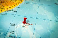 Red thumbtack in a map, pushpin pointing at Seychelles island - stock photo