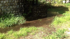 Small river flowing aroung stone basement of water mill, Japan Stock Footage