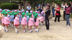 Small Asian girls in pink and blue coats flaping hands with teacher outdoor Stock Footage