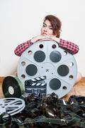 Young woman sitting behind big cinema movie reel - stock photo