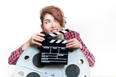 Young woman with movie clapper behind big cinema reel - stock photo