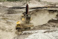 Excavator at work in the open-pit mine - industrial machinery digger coal lig Stock Photos