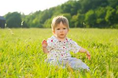 Babe sit on the grass. - stock photo