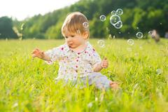 Babe playing on the lawn. - stock photo