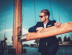 Stylish wealthy man on a luxury wooden regatta - stock photo