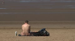 topless man sitting alone on beach - stock footage