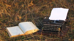 Manual Typewriter And Opened Book On The Grass At Meadow Stock Footage