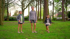 Young girls chasing down a ball in a park Stock Footage
