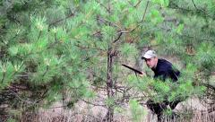 Hunter sneaks up behind the trees Stock Footage