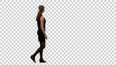 An elegant woman walking and watching something (on alpha matte), Back view - stock footage