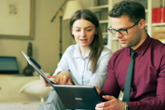 Businesscuple working together on graphs at home Stock Footage