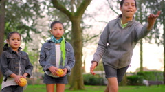 Young girls throwing balls at a park Stock Footage