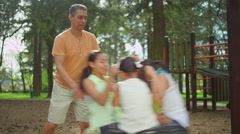 Father pushing his daughters on a tire swing in a park Stock Footage