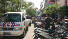 Small truck rush through parking area, many motorbikes standing aside Stock Footage