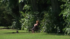 Woman on bench in sun with dog at feet in park Stock Footage