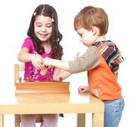 Brother and sister in Montessori kindergarten work with the puzz - stock photo