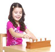 The dark-haired little girl in a Montessori kindergarten works w - stock photo