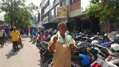 Motorbike parking, man show cash note and thumb up, pose on camera Stock Footage