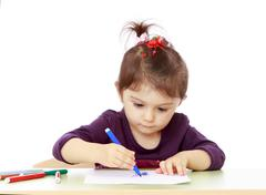 Keen little girl draw with felt-tip pen sitting at the table - stock photo
