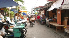 Walk on sunny narrow market street, people, bajaj, motorbike, stalls, wheel cart Stock Footage
