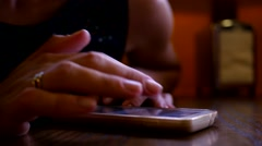 Close-up of girl sliding phone touch screen in pub viewing social network public Stock Footage