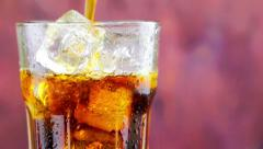 Pouring fresh coke with ice cubes into glass with drops on wood background Stock Footage