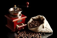 Bag full of coffee beans with mill on black - stock photo