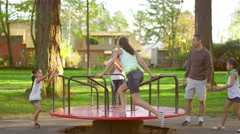 Family playing on a merry-go-round at a park - stock footage