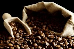 Overturned sack full of coffee beans isolated on black with spatula Stock Photos