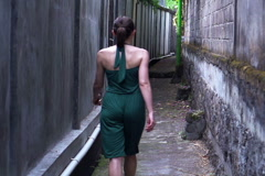 Young woman walking through narrow urban path NTSC Arkistovideo