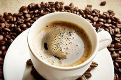 Macro studio shot of frothy black coffee, plenty of coffee beans view at brea - stock photo