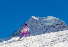Little skier in high mountains Stock Photos
