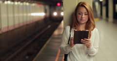 Young Caucasian woman at subway platform using tablet pc - stock footage
