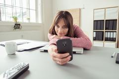Bored woman in the office checking her mobile - stock photo
