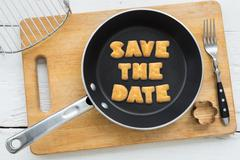 Letter biscuits quote SAVE THE DATE and cooking equipments. Stock Photos