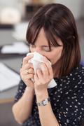 Sick Businesswoman Sneezing Into a Tissue Stock Photos
