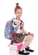 Serious, elegantly dressed schoolgirl sitting on a stack of book Stock Photos