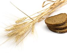 The cut bread and ears of wheat Stock Photos