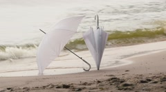 Two white umbrella on a background of water Stock Footage