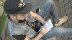 A young man wearing a cap in the notebook draws a graph and figures. Stock Footage