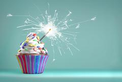 Delicious cupcake with a sparkler for an event celebration. - stock illustration