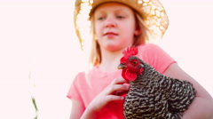 Young girl standing in a backyard holding a chicken Stock Footage