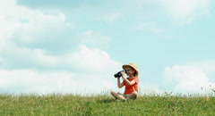 Young naturalist through binoculars watching wildlife and looking at camera. - stock footage