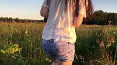 Girl in denim shorts goes through the long grass Stock Footage
