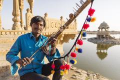 Indian man holding traditional instrument near monument, Jaisalmer, Rajasthan, Stock Photos